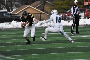 UWO running back J.P. Peerenboom protects the ball on one of his eight carries against UW-Stout.