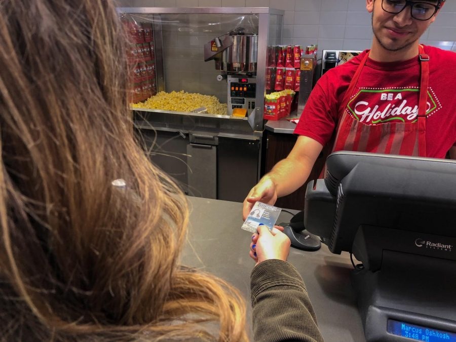 A UW Oshkosh student shows her Titan ID to an employee at the Marcus Oshkosh Cinema for a discount.