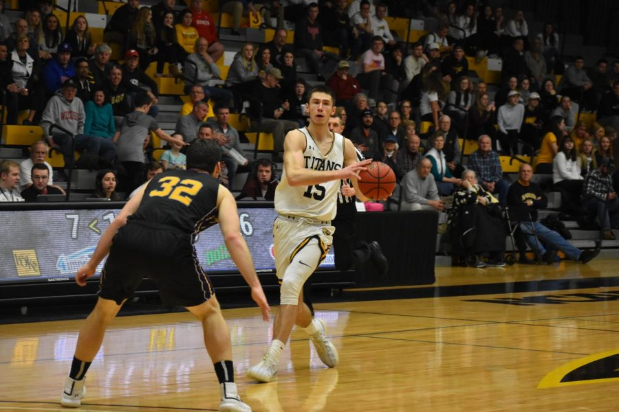 UWO+junior+forward+Adam+Fravert+passes+the+ball+against+a+UW-Stevens+Point+player+last+Thursday.+Fravert+scored+eight+points+to+go+along+with+five+rebounds+and+two+assists.+The+Titans+shot+13+percent+from+the+three-point+line+in+the+loss.+