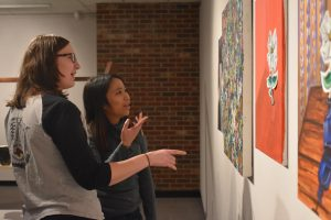 Seniors Rachel Blohowiak and Colleen Montevilla look at the 19th Annual Honors Exhibition pieces.
