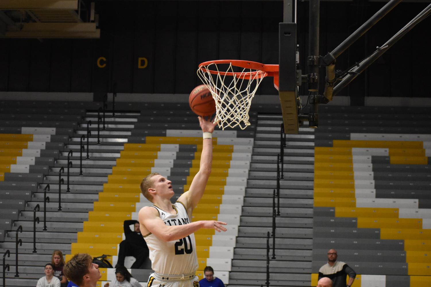 UW Oshkosh sophomore forward Connor Duax attempts a layup in front of an empty Kolf Sports Center.