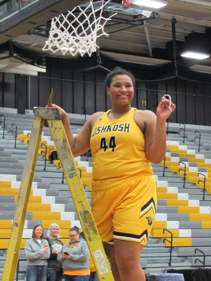 UWO senior Isabella Samuels cuts her piece of the net after recording 10 points in the WIAC Championhip.
