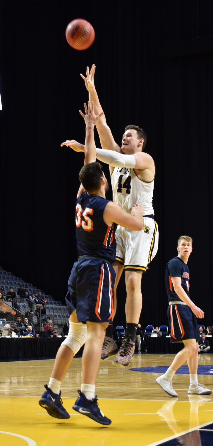 UWO junior center Jack Flynn shoots a floater over Wheaton College junior Spencer Peterson during the Titans' victory over the Thunder. Flynn scored 21 and pulled down 15 rebounds for UWO.