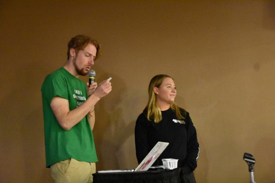 Students Collin Brault and Morgaine Prather read off winning raffle tickets at a trivia night event hosted in the Titan Underground.
