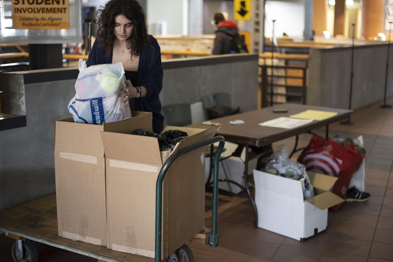 Mary-Rachel Novak, a Clothes the Loop volunteer, organizes donations for a recycling program.