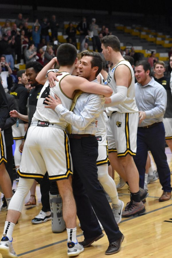 Brett Witchow hugs one of the  Men's Basketball assistant coaches, Ben Stelzer