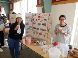 Students pose in front of their poster for UW-Fox Valley's fifth international student event.