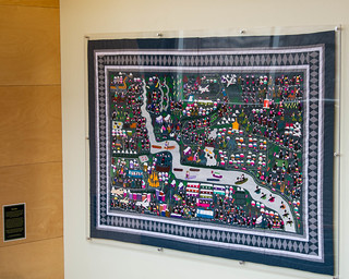 Paj Ntaub, a Hmong story cloth, is displayed. The cloths document daily experiences and hardship.