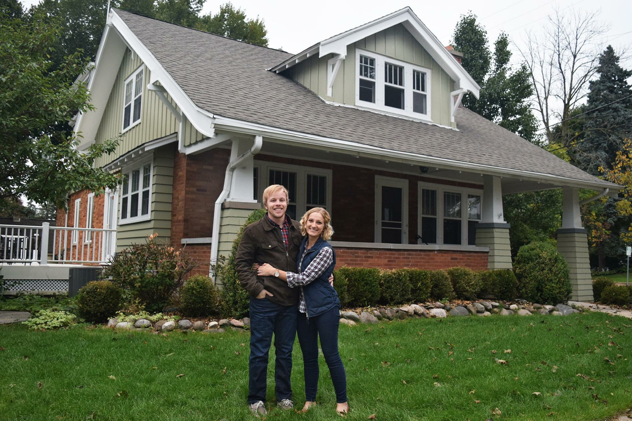 UWO alumni Josh and Alli (Kerwin) Hughes happily pose in front of their new Waukesha home.
