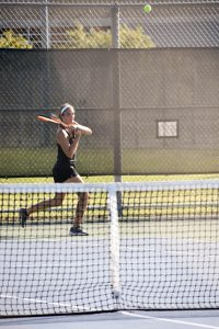 Junior Alyssa Leffler returns a ball over the net in Sunday's home match against Cathage College.