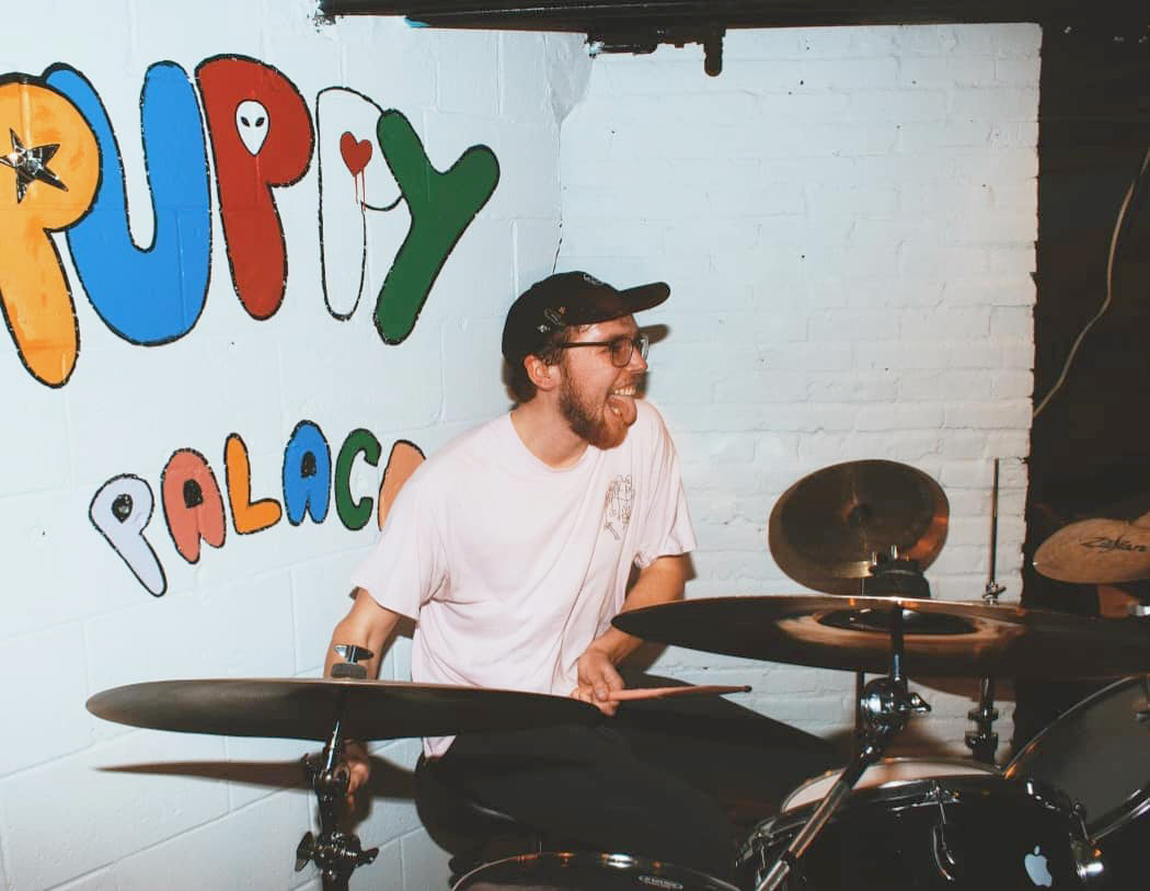 Nosebleeds drummer Paul St. Aubin plays at The Puppy Palace under its freshly painted backdrop. Nosebleeds are one of the original bands to play at The Puppy Palace and have their debut album Good Boy available on all streaming services.