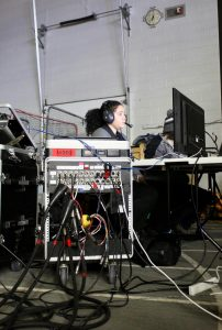 Titan TV Programming Director Crystal Perez runs audio and graphics at a basketball game.
