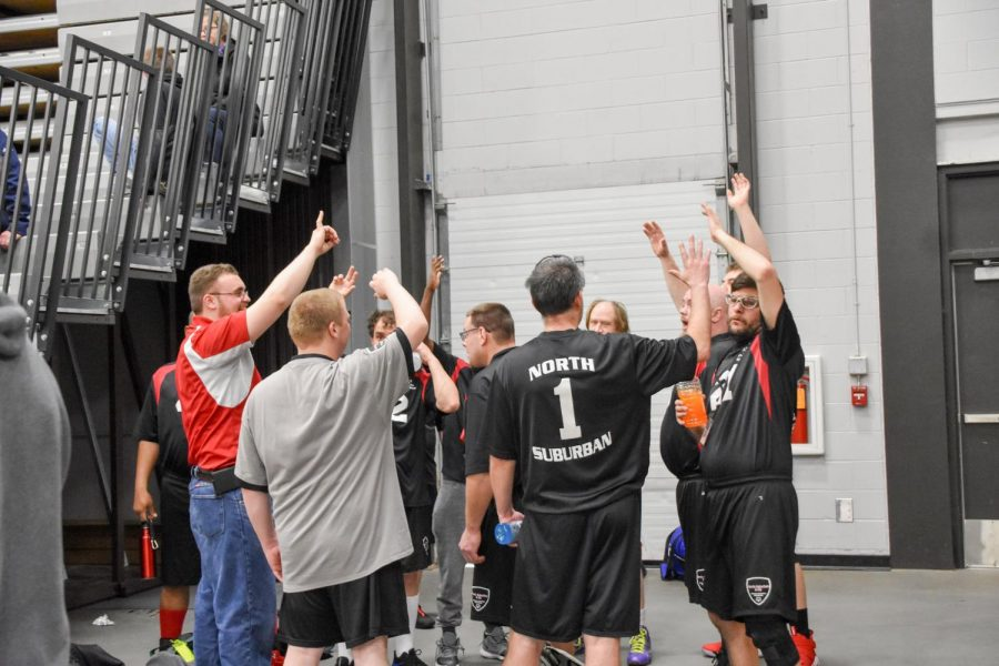North Suburban players and coaches high-five in celebration of a well-played game.