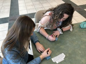 Maddie Nolan and Savanna Peterson write supportive messages for sexual assualt awareness.