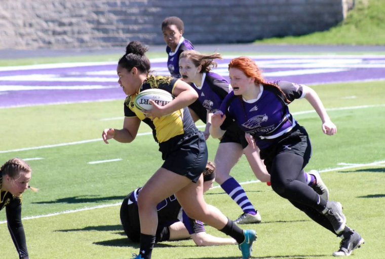 Titan forward carries the ball through UW-Whitewater defenders. UWO split their team in two and took first and second.