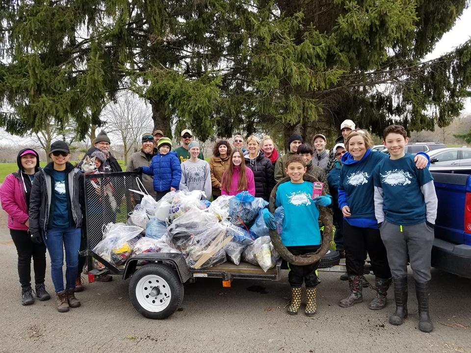 Some of the 1,100 Fox-Wolf Watershed volunteers pose with collected garbage by the Fox River on April 27.