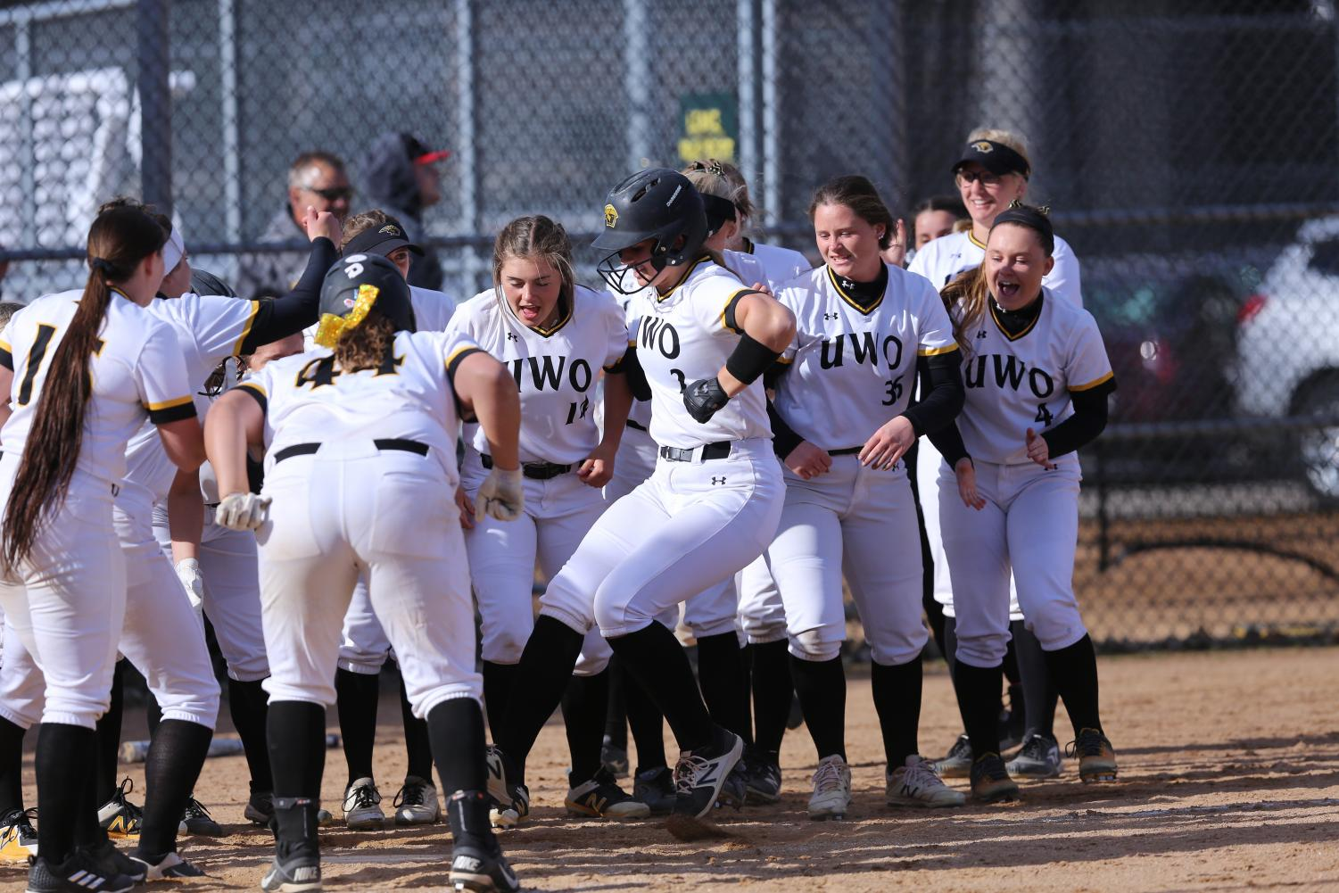Abby Menting celebrates with her team at home plate after her fourth-inning homerun versus UW-Eau Claire.