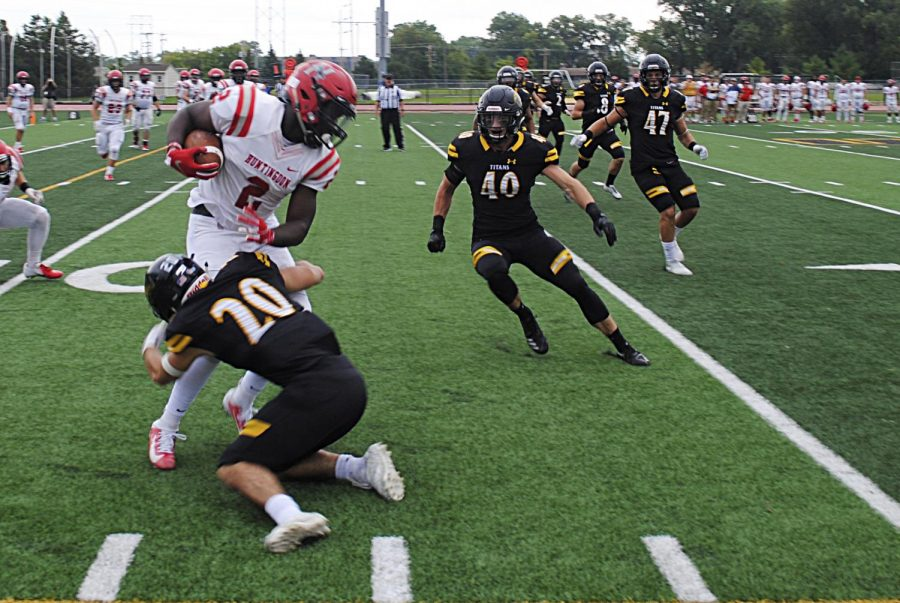 UWO senior defensive back Calvin Shilling (20) tackles Huntingdon quarterback Otis Porter (2) while UWO linebacker Nick Noethe approaches in pursuit. Shilling recorded three total tackles in the 44-14 victory for the Titans.