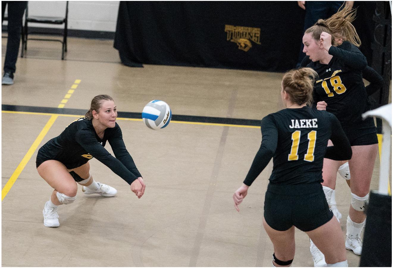 UW Oshkosh sophomore Becky Brezen (21) passes a ball against Oswego State while senior Sam Jaeke (11) and freshman Kate Nottoli (18) set up to receive the pass. The Titans won the match 3-0.