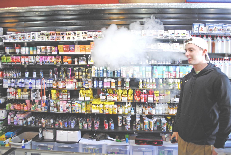 A-Z Tobacco & Vapor Shop clerk Jordan Treichel exhales a cloud of vapor in front of vape juices.