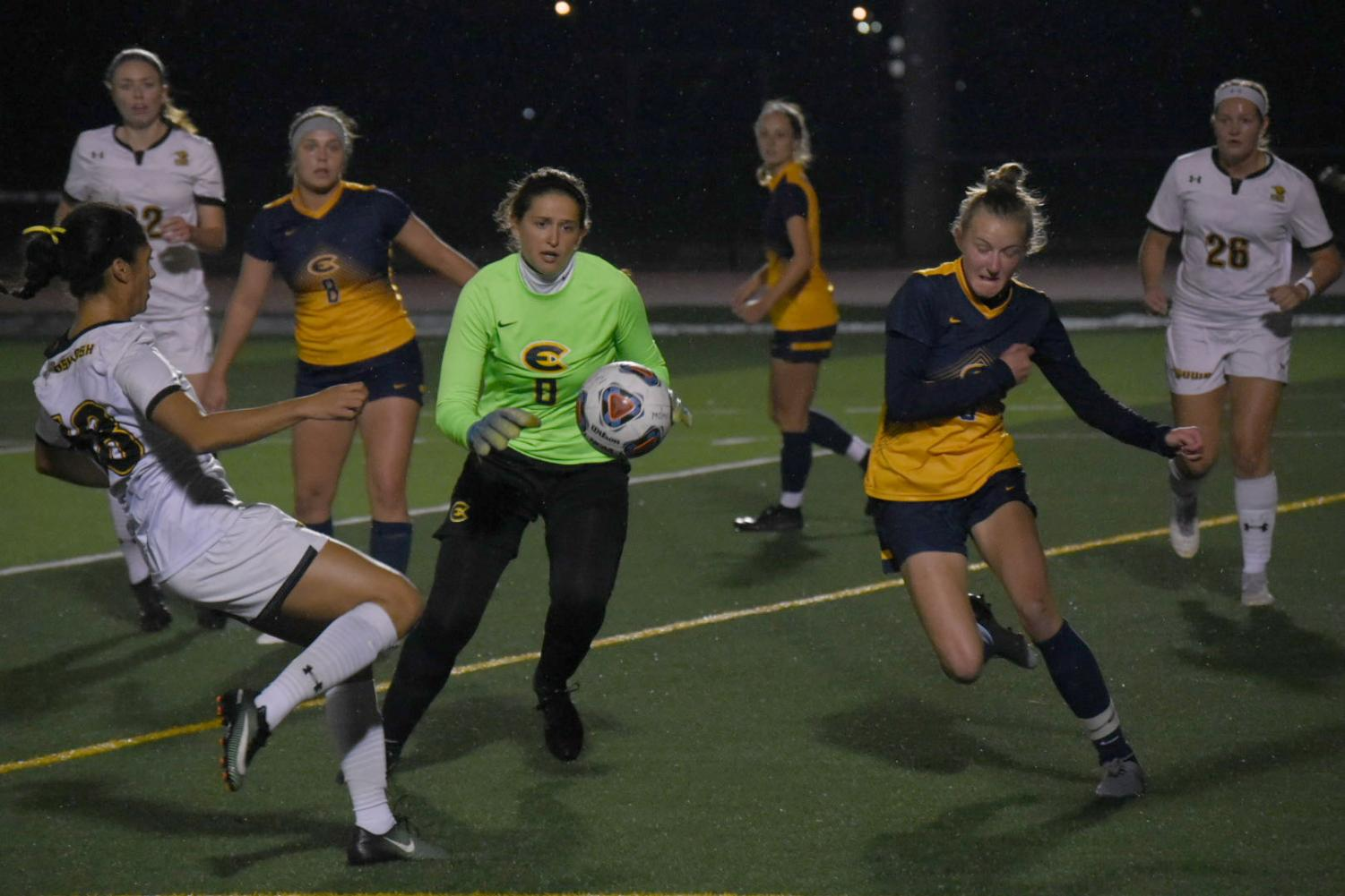 Senior Madison Smith approaches UW-Eau Claire defenders while two of her teammates look on.