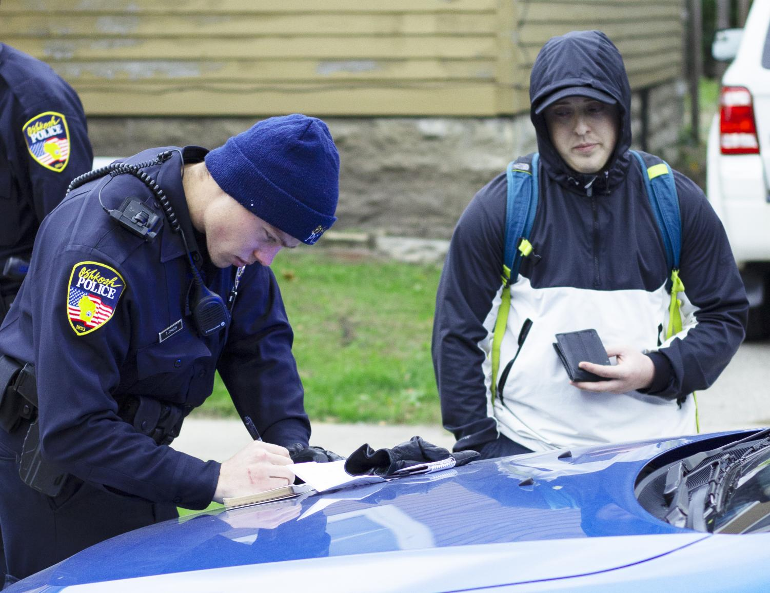 A police officer writes an open-intoxicant ticket. /