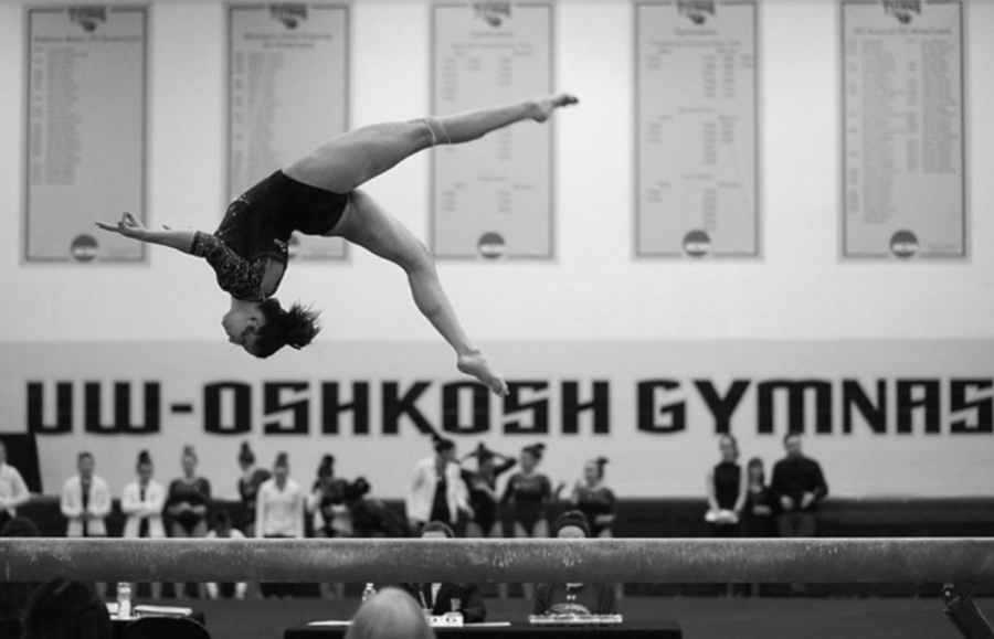 Courtesy of UW Oshkosh Photoshelter Junior Paige Mayhew  performs an aerial on the balance beam at a home meet on Jan. 17, 2020.