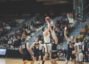Senior center Jack Flynn tosses up a floater over UW-Eau Claire forward Spencer Page in UW Oshkosh's 78-72 WIAC Championship home victory on Feb. 29. Flynn put up 19 points, eight rebounds and one assist. The Titans will ride their seven-game winning streak into Naperville, IL to play Transylvania University.