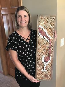 Laurens mother, Jennifer, holds the cork board Lauren made for her birthday