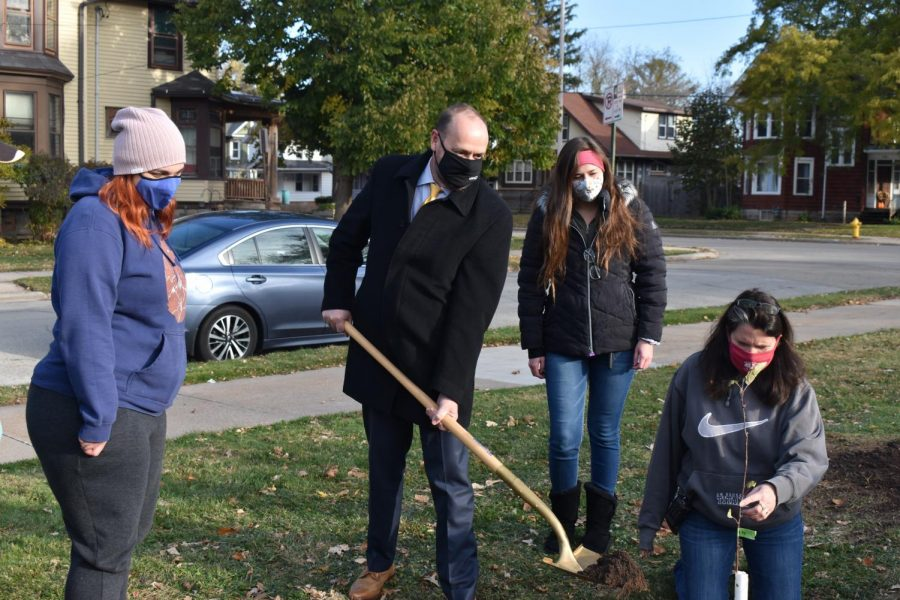 Chancellor Andrew Leavitt shovels dirt into the Ratzburg apple tree sapling hole while Lisa Mick supports the sapling.
