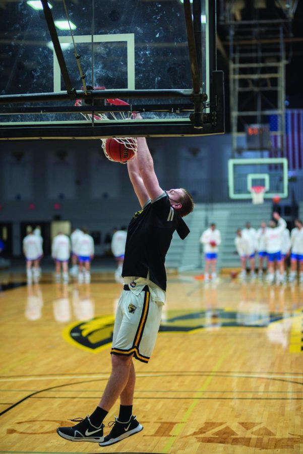 April Lee / Advance-Titan | Freshman center Joseph Adamson slams the ball in warm-ups before the Titans' 77-68 win over the Pioneers in the Feb. 5 matchup at the Kolf Sports Center.