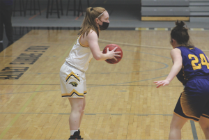 Katie Pulvermacher / Advance-Titan Freshman guard Lydia Crow surveys the court as she prepares to pass the ball in the Feb. 17 matchup against UWSP at the Kolf Sports Center. UWO went on to win the matchup by a score of 75-45, making the game their largest blowout win of the year.