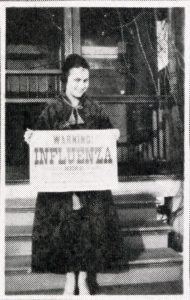 A female student holds a sign on the steps of her home in 1918, warning people not to enter because of influenza. (University Archives photo)