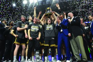 The 2019 Titan men's basketball team holds up the championship trophy in front of their faithful fans as confetti rains down around them. It is their first national championship in program history. (Advance-Titan file photo)
