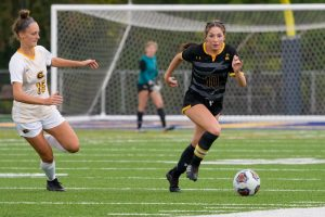 Photo courtesy Terri Cole — Alexia Poulos tears down the field, keeping the ball away from UW-Eau Claire.